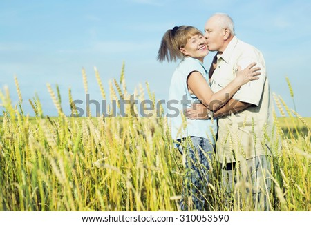 happy couple: sixty eight year old man and sixty five year old woman outdoor at the wheat field - stock photo