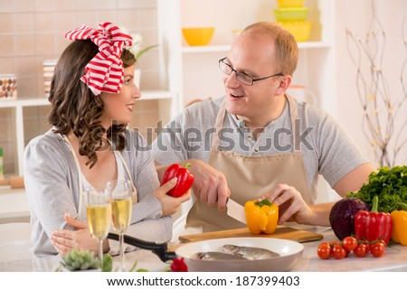 Happy couple slicing pepper food in the kitchen