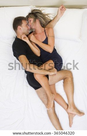Happy couple smiling and hugging on the bed top view - stock photo