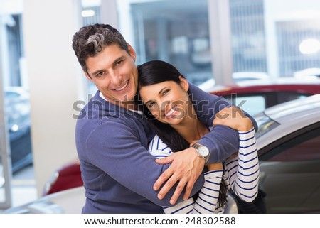 Happy couple smiling at camera and embracing at new car showroom - stock photo