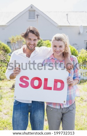 Happy couple smiling at camera holding sold sign at home in the garden
