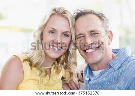 Happy couple smiling at camera in the living room - stock photo