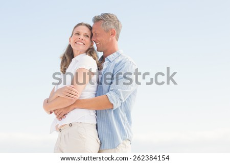 Happy couple smiling at each other at the beach - stock photo