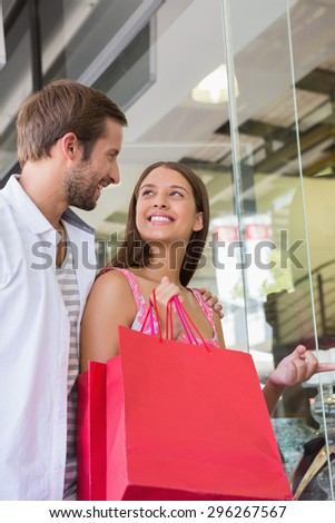 Happy couple smiling at each other in front of a clothing shop
