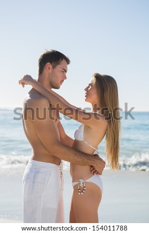 Happy couple speaking and embracing on the beach - stock photo