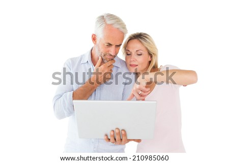 Happy couple standing and using laptop together on white background - stock photo