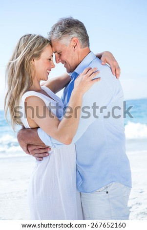 Happy couple standing by the sea and hugging each other at the beach - stock photo