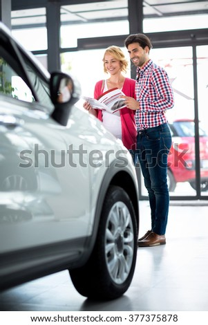 Happy couple standing front  of his favorite model of car in car showroom - stock photo
