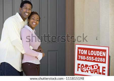 Happy couple standing in front of their new home