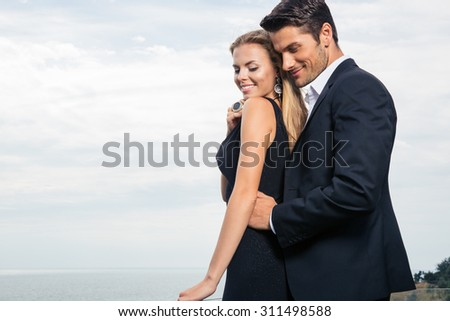 Happy couple standing outdoors - stock photo