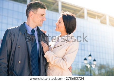 Happy couple standing outdoors and looking to each other with glass building on background - stock photo