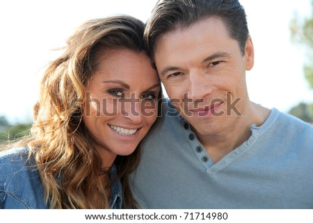 happy couple standing outside on a sunny day - stock photo