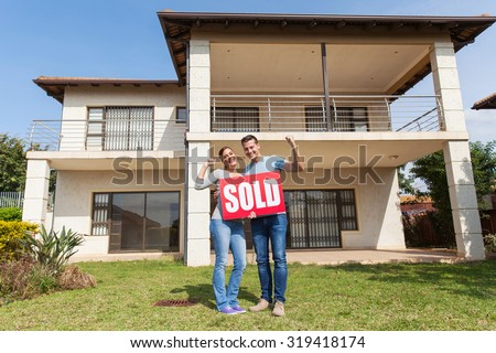 happy couple standing outside their house and holding sold sign - stock photo