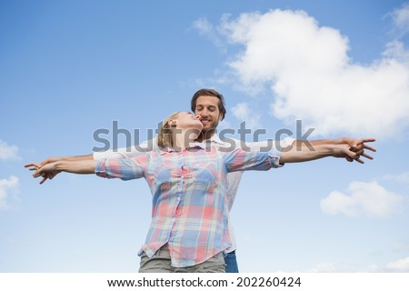 Happy couple standing outside with arms stretched kissing on a sunny day
