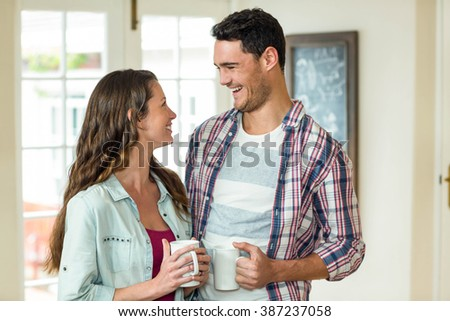 Happy couple standing with cup of tea and looking each other