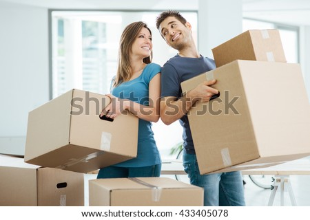 Happy couple staring at each other eyes and carrying boxes in their new house - stock photo