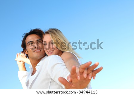 Happy couple stretching arms at the beach