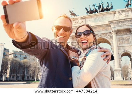 Happy couple take a selfie photo on the Arch of Peace in Milan - stock photo