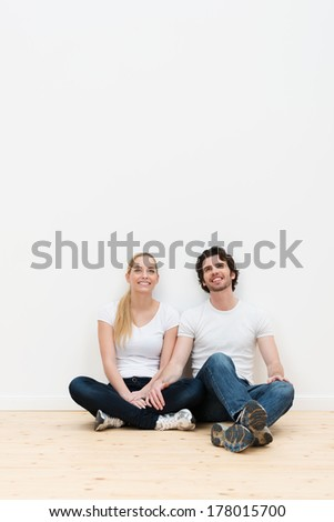 Happy couple taking a break during a house move sitting on the bare wooden floor of their new home with their backs against a white wall with copyspace - stock photo