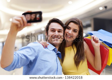 Happy couple taking a photo during a shopping - stock photo