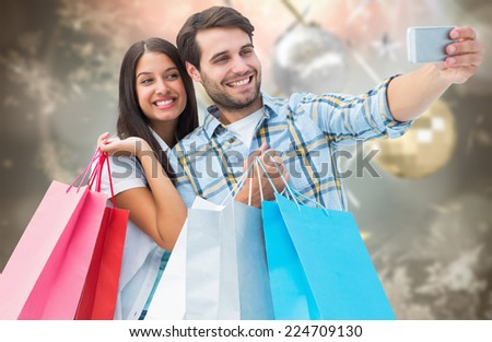 Happy couple taking a selfie against blurred christmas background - stock photo
