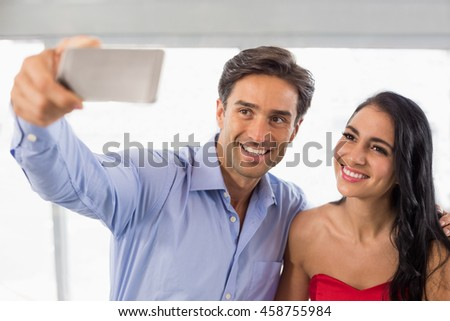 Happy couple taking a selfie in cafe