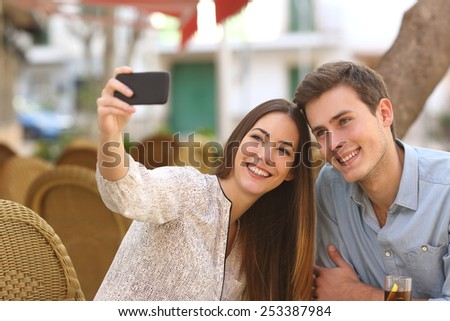 Happy couple taking a selfie photo with a smart phone in a restaurant terrace - stock photo