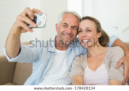 Happy couple taking a selfie together on the couch at home in the living room - stock photo