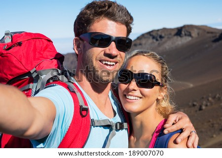 """Happy couple taking photo of themselves with smart phone outdoors, Taking a """"selfie"""" - stock photo"""