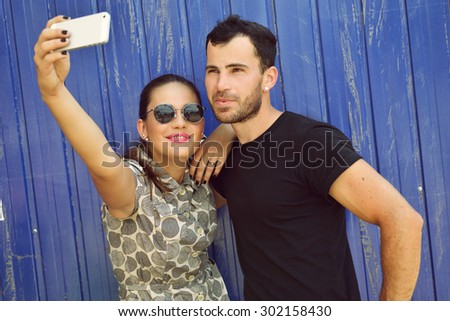 Happy couple taking self photo with smart phone. Selfie, love, relationship, young adult, concept. Image toned. - stock photo