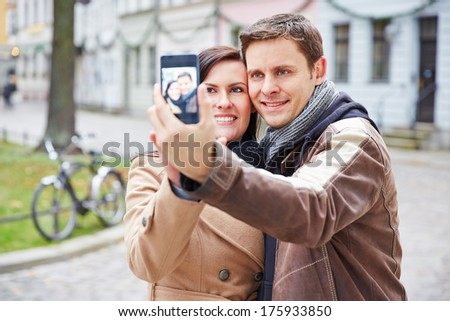 Happy couple taking self portrait with smartphone in an autumn city - stock photo