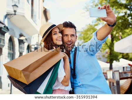 Happy couple taking selfie after shopping in the city - stock photo