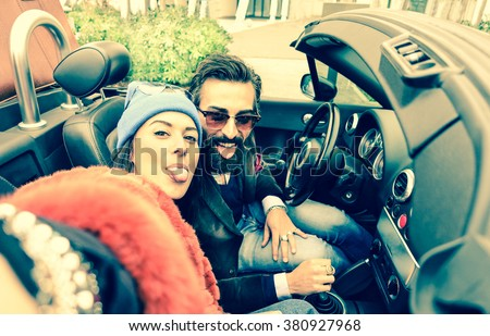 Happy couple taking selfie at car trip - Young tourists having fun together traveling around Europe - Technology addiction and fashion lifestyle concept - Vintage filter with main focus on her - stock photo