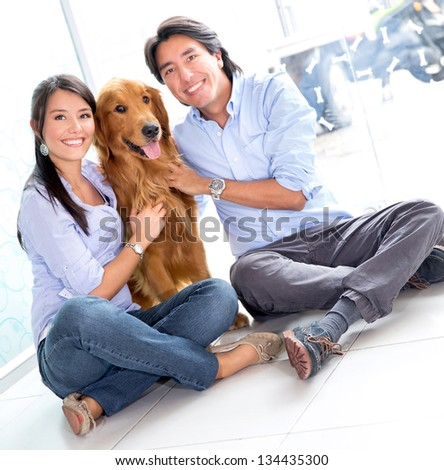 Happy couple taking their beautiful dog to the vet - stock photo