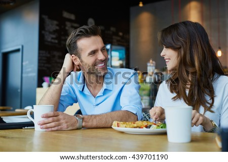 Happy couple talking at cafe, eating lunch