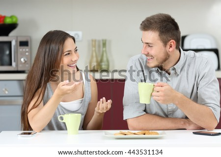 Happy couple talking sitting in the kitchen at breakfast - stock photo