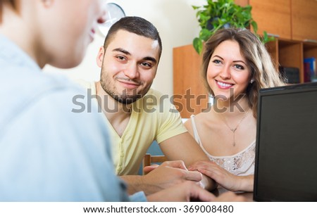 Happy couple talking with employee with laptop at home - stock photo