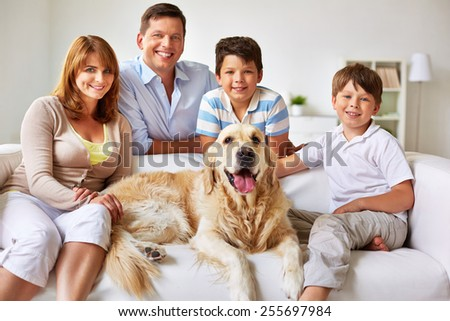Happy couple, their two sons and dog - stock photo