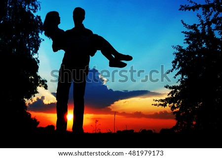 happy couple together at sunset silhouette of nature