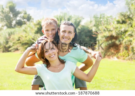 Happy couple together with teenager in summer park