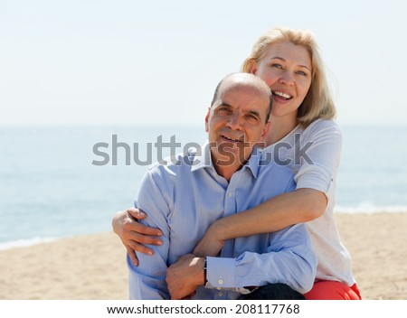 Happy couple tourists at beach on vacation smiling together