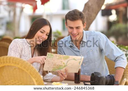 Happy couple tourists consulting a guide in a restaurant terrace - stock photo