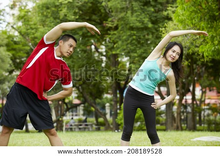 Happy couple training in the park - Young man and woman during summer workout and sport activity - stock photo
