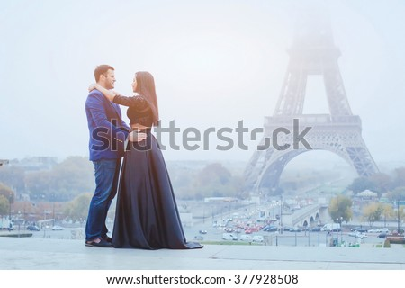 happy couple traveling in Paris, smiling man and woman posing in fancy fashion clothes on Eiffel Tower background during their honeymoon - stock photo