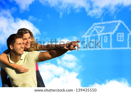 Happy couple under the blue sky enjoying the sun pointing to a house made of clouds.