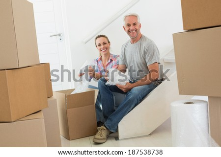 Happy couple unpacking cardboard moving boxes in their new home