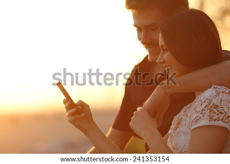 Happy couple using a smartphone in a sunset back light on the beach - stock photo