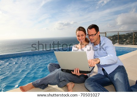 Happy couple using laptop computer by swimming-pool - stock photo