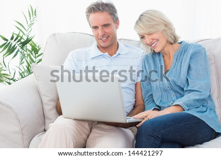 Happy couple using laptop together on the couch at home in living room