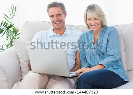 Happy couple using laptop together on the couch looking at camera at home in living room
